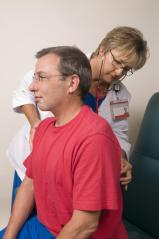 This image depicts a female clinician using a stethoscope she'd placed upon a male patient's back.
