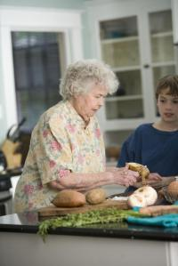 Elderly woman teaching her grandson how to peel a sweet potato.